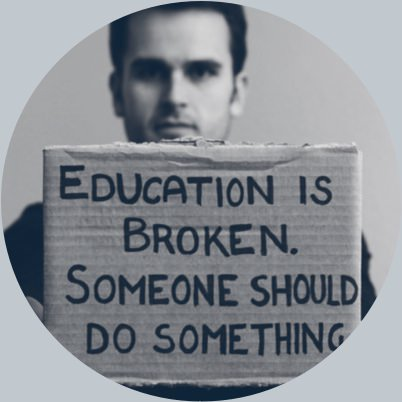David Blake holding cardboard sign: 'Education is broken. Someone Should Do Something.'